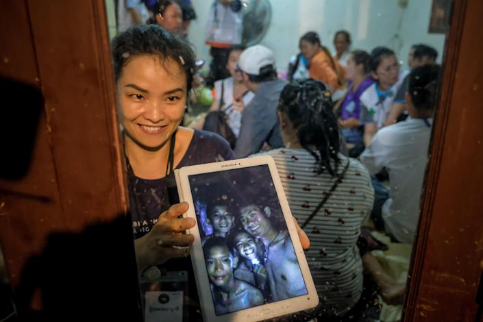 <p>Relatives show photos on tablets of the some of the 12 boys who were found alive in a cave where they'd been lost for over a week along with their soccer coach, in Chiang Rai, Thailand. Gov. Narongsak Osatanakorn announced on July 2 that the boys, aged 11 to 16, and their 25-year-old coach were being rescued from Tham Luang Nang Non cave. (Photo: Linh Pham/Getty Images) </p>