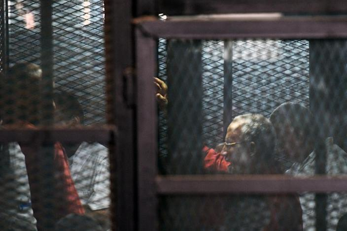 Egyptian Muslim Brotherhood leader Mohamed Badie (2nd-R) stands behind bars during a trial in Cairo on August 22, 2015 (AFP Photo/Mohamed el-Shahed )