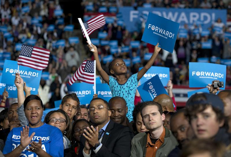 Amara Hayles, 6, of Columbus, sits atop her dad, Marlon Hayles, shoulders and waves a American flag as President Barack Obama speaks at a campaign event at Nationwide Arena, Monday, Nov. 5, 2012, in Columbus, Ohio. (AP Photo/Carolyn Kaster)