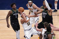 Denver Nuggets' Aaron Gordon (50) shoots as Minnesota Timberwolves' Karl-Anthony Towns (32) defends and Anthony Edwards (1) watches during the first half of an NBA basketball game Thursday, May 13, 2021, in Minneapolis. (AP Photo/Jim Mone)