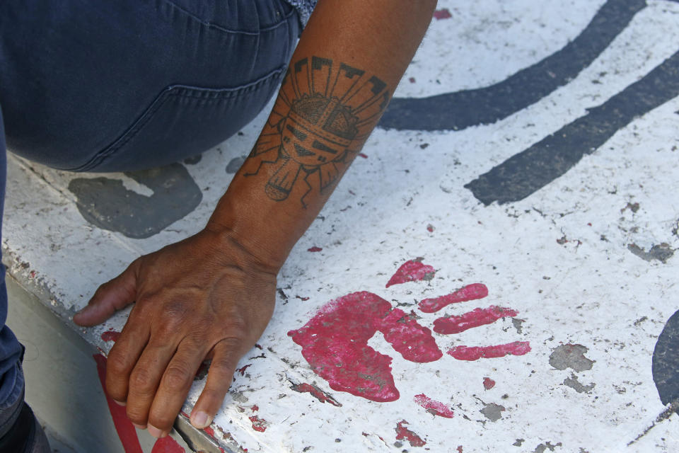 Native American advocate Carl Moore sits next to red handprint painted along a walkway which leads from the Bountiful High School parking lot up to the football field Tuesday, July 28, 2020, in Bountiful, Utah. While advocates have made strides in getting Native American symbols and names changed in sports, they say there's still work to do mainly at the high school level, where mascots like Braves, Indians, Warriors, Chiefs and Redskins persist. (AP Photo/Rick Bowmer)