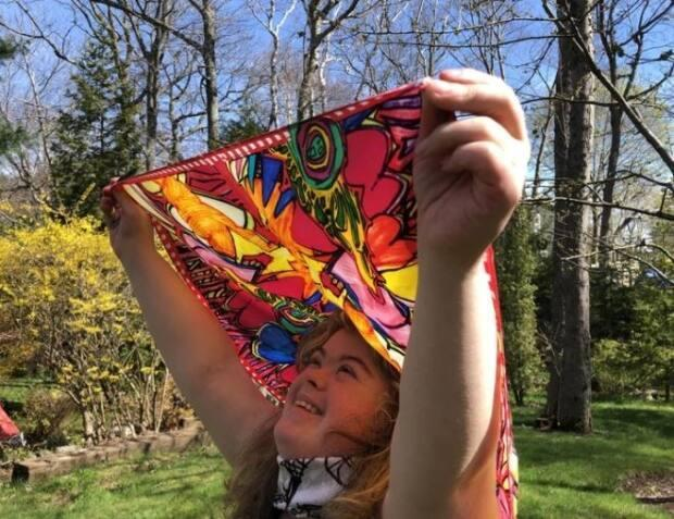 Marie Webb shows off  a scarf printed with her 'girl power' design from her Necklings collection.