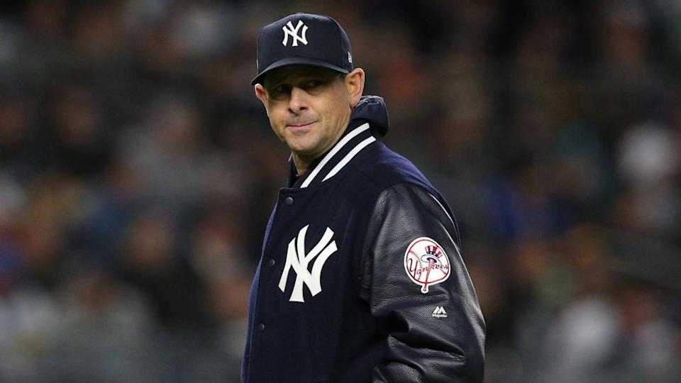 Yankees manager Aaron Boone on field during night game wearing bomber jacket, close crop
