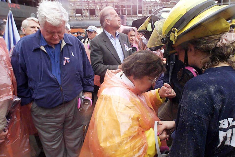 FILE - In this Sept. 20, 2001, file photo Sen. Ted Kennedy, D-Mass., left, and Sen. Joe Biden, center, stand by as Sen. Barbara Mikulski, D-Md., in orange parka, joins in prayer with rescue workers at the site of the World Trade Center in New York. They were part of a delegation of Senators that traveled by train to New York to view the rubble that once was the World Trade Center. The terrorist attacks that day shattered Americans' sense of security and ushered in a new era of nebulous threats, hidden enemies and a seemingly never-ending war on terror. And for then-Sen. Joe Biden they marked a new phase of his public life. (AP Photo/Mike Albans, Pool, File)