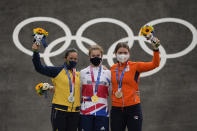 Bethany Shriever of Britain, center, Mariana Pajon of Colombia, left, and Merel Smulders of the Netherlands, right, stand with their medals in the women's BMX Racing finals at the 2020 Summer Olympics, Friday, July 30, 2021, in Tokyo, Japan. (AP Photo/Ben Curtis)