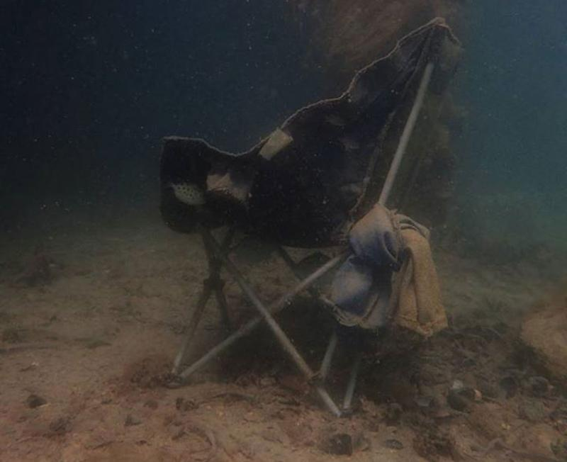A discarded camp chair underwater.