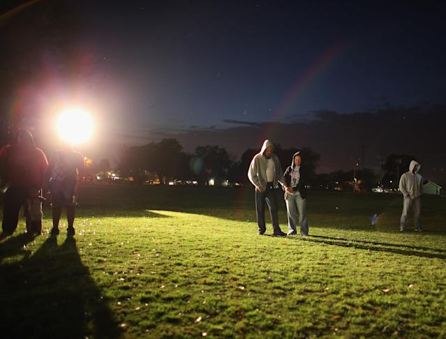 SANFORD, FL - FEBRUARY 26: Sal Guardino and Elizabeth Buszta (L-R) stand together during a prayer before lighting candles during a vigil at Fort Mellon Park to mark the one year anniversary of when Trayvon Martin was killed on February 26, 2013 in Sanford, Florida. Martin was shot by George Zimmerman on February 26, 2012 while Zimmerman was on neighborhood watch patrol in the gated community of The Retreat at Twin Lakes in Sanford, Florida. (Photo by Joe Raedle/Getty Images)