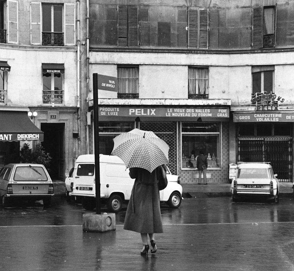 A woman gets caught in a rainfall on the Rue de Rivoli, one of the most famous streets in Paris.