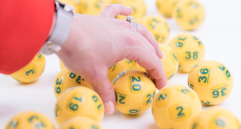 A woman's hand reaches towards yellow Oz Lotto playing balls.