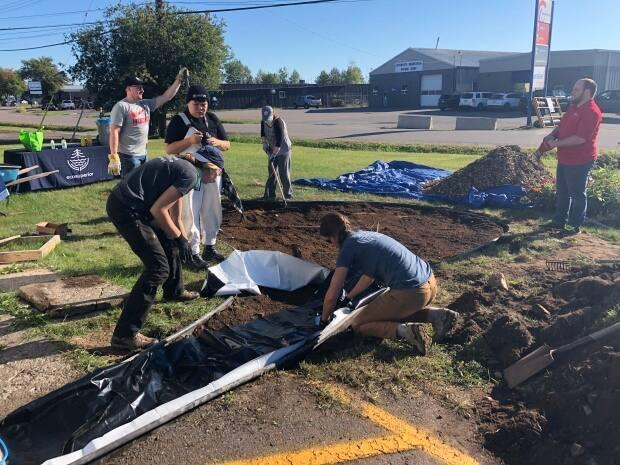 Volunteers help build a rain garden in front of Habitat for Humanity's office and ReStore in Thunder Bay, Ont. (Jeff Walters/CBC - image credit)