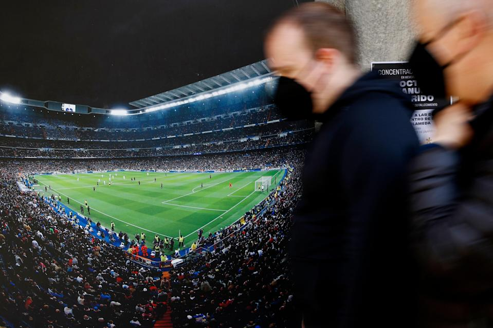 Soccer Football - Twelve of Europe's top football clubs launch a breakaway Super League - Madrid, Spain - April 20, 2021   People walk past a picture of the Santiago Bernabeu Stadium as twelve of Europe's top football clubs launch a breakaway REUTERS/Susana Vera (Photo: SUSANA VERA via REUTERS)