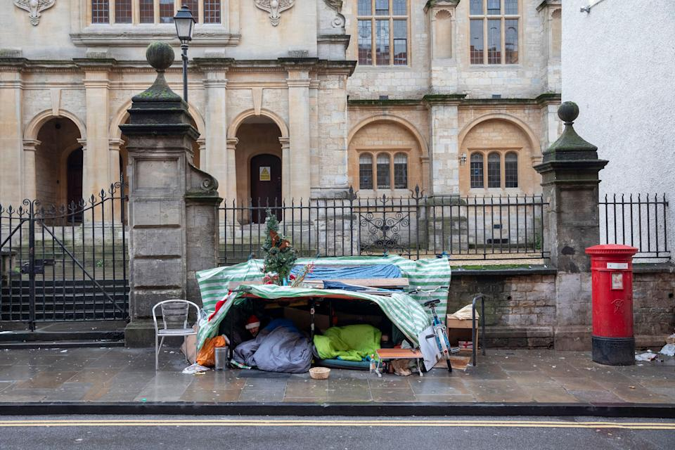Two homeless men sleeping under a makeshift tent with festive decorations in Oxford, 2019. (Photo: Sam Mellish via Getty Images)