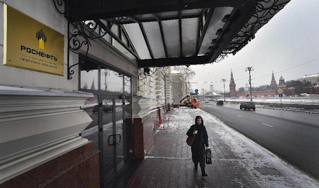 A woman walks past the headquarters of Russia's state-controlled oil giant Rosneft in Moscow (AFP Photo/Alexander Nemenov)
