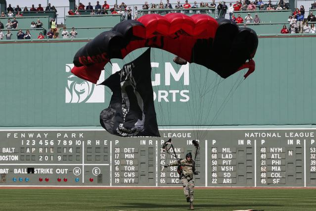A member of the U.S. Army Black Daggers Parachute Demonstration Team lands on the field at Fenway Park before a baseball game between the Boston Red Sox and the Baltimore Orioles in Boston, Sunday, April 14, 2019. (AP Photo/Michael Dwyer)