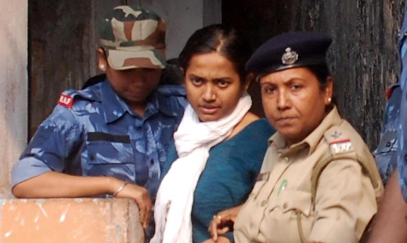 Police officials escort local Bharatiya Janata Party (BJP) politician Juhi Chowdhury after her arrest in Siliguri