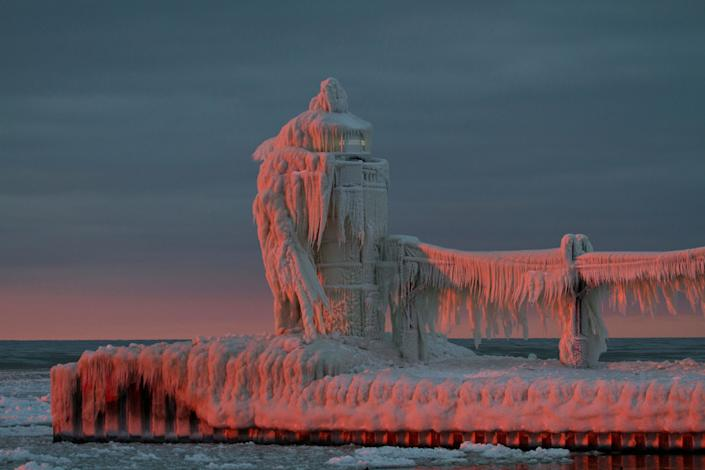 """The lighthouse in St. Joseph, Michigan, has become an ice sculpture. Yesterday (January 26, 2013), after a day of cloudy skies, there was a break in the clouds just above the horizon to the west. As the sun slipped below the the bank of clouds the ice-covered lighthouse came alive in hues of pink. This was one of the most stunning natural wonders I've ever seen. (Photo and caption Courtesy Lisa Rundell / National Geographic Your Shot) <br> <br> <a href=""""http://ngm.nationalgeographic.com/your-shot/weekly-wrapper"""" rel=""""nofollow noopener"""" target=""""_blank"""" data-ylk=""""slk:Click here"""" class=""""link rapid-noclick-resp"""">Click here</a> for more photos from National Geographic Your Shot."""