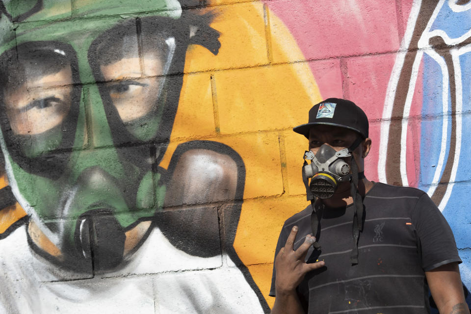 Graffiti artist Angelo Campos poses for a photo by his mural referencing the COVID-19 pandemic which he said he painted in honor of health workers in Rio de Janeiro, Brazil, Thursday, May 21, 2020. (AP Photo/Silvia Izquierdo)
