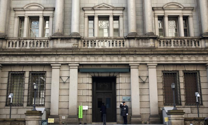 A security guard salutes at the entrance of the Bank of Japan building in Tokyo
