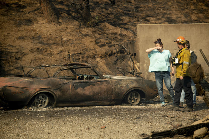 A resident surveys the scorched remains of her home and vehicle after the Saddleridge Fire burned through Granada Hills, Calif., on Friday, Oct. 11, 2019. (AP Photo/Noah Berger)
