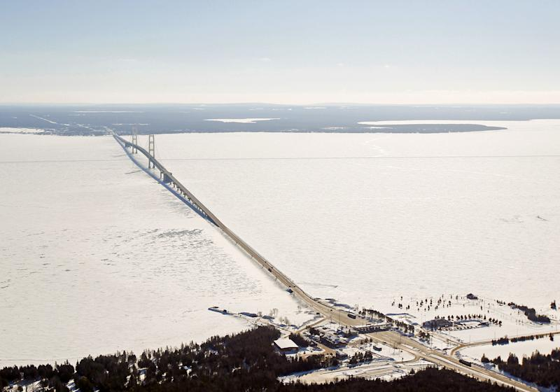 In this Feb. 11, 2014 aerial photo is a view of The Mackinac Bridge which spans a 5-mile-wide freshwater channel that separates Michigan's upper and lower peninsulas. The straits is drawing the attention of some who consider the twin 20-inch pipes that stretch across the bottom of the waterway, carrying nearly 23 million gallons of crude oil daily, a symbol of the dangers lurking in the nation's sprawling web of buried oil and natural gas pipelines. (AP Photo/ Traverse City Record-Eagle, Keith King, Pool)