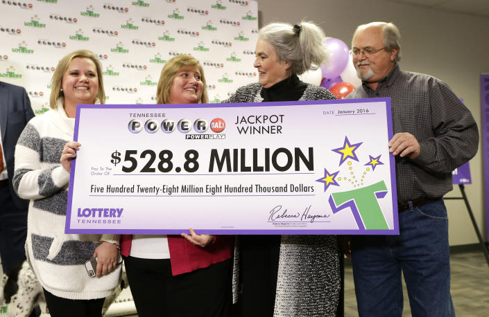 Rebecca Hargrove, second from right, president and CEO of the Tennessee Lottery, presents a ceremonial check to John Robinson, right; his wife, Lisa, second from left; and their daughter, Tiffany, left; after the Robinsons' winning Powerball ticket was authenticated at the Tennessee Lottery headquarters on Friday in Nashville, Tenn. The ticket was one of three winning tickets in the $1.6 billion jackpot drawing. (AP Photo/Mark Humphrey)