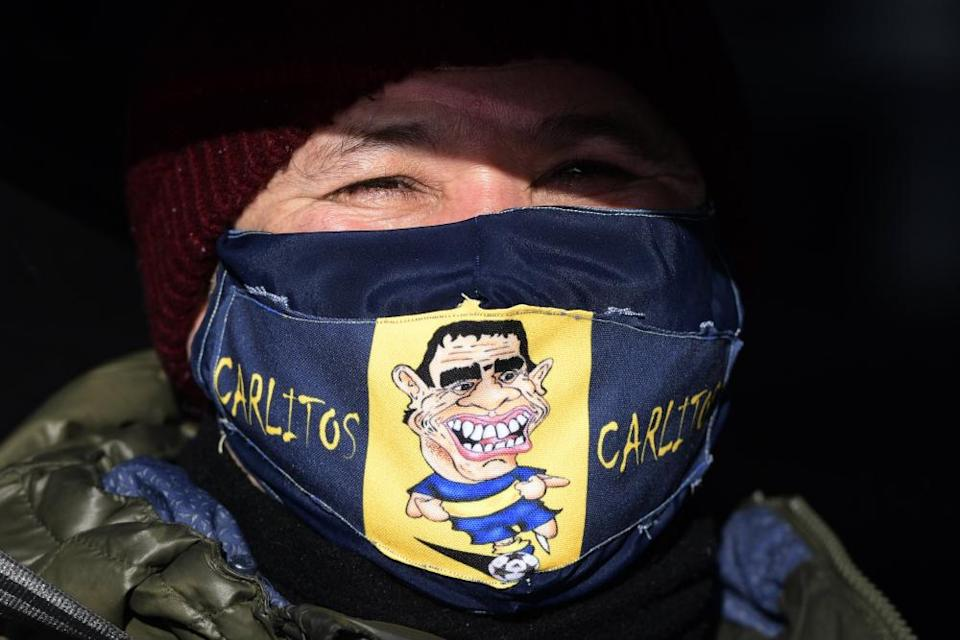 A man wearing a mask with a cartoon Carlos Tévez in Buenos Aires.
