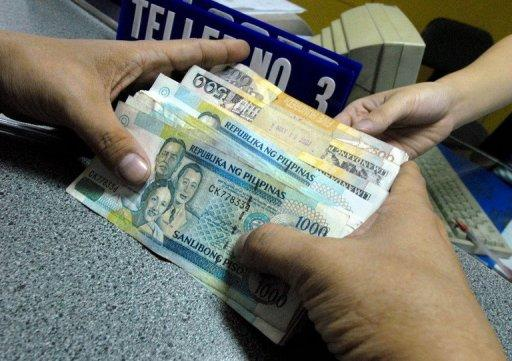 FILE PHOTO: A customer holds Philippine peso notes during a bank transaction in Manila. (Photo: Getty Images)