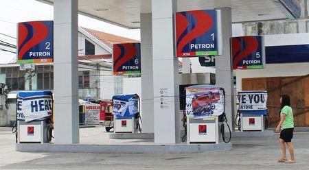 A woman walks past a petrol station that is closed due to super-typhoon Hagupit in Tacloban city, central Philippines December 5, 2014. REUTERS/Rowel Montes