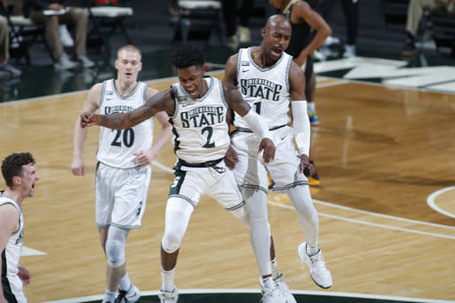 Michigan State's Joshua Langford, right, and Rocket Watts (2) celebrate along with Joey Hauser (20) and Foster Loyer, left, during the first half of the team's NCAA college basketball game against Purdue on Friday, Jan. 8, 2021, in East Lansing, Mich. (AP Photo/Al Goldis)