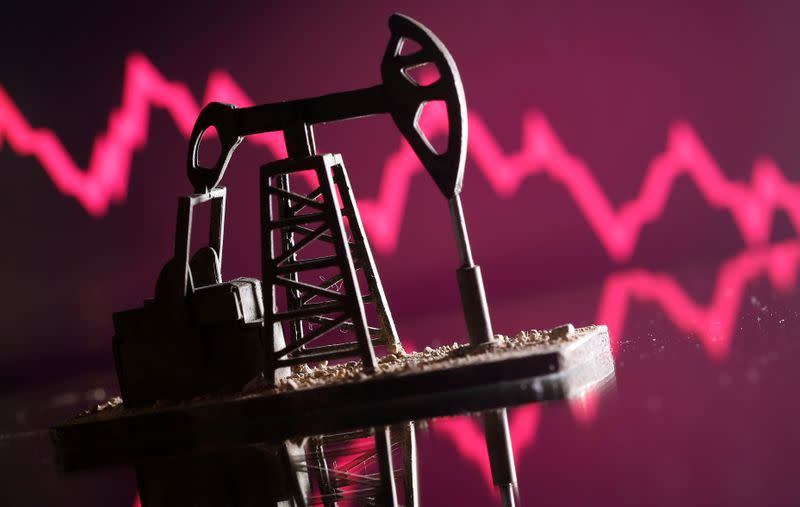 A 3D printed oil pump jack is seen in front of displayed stock graph in this illustration picture