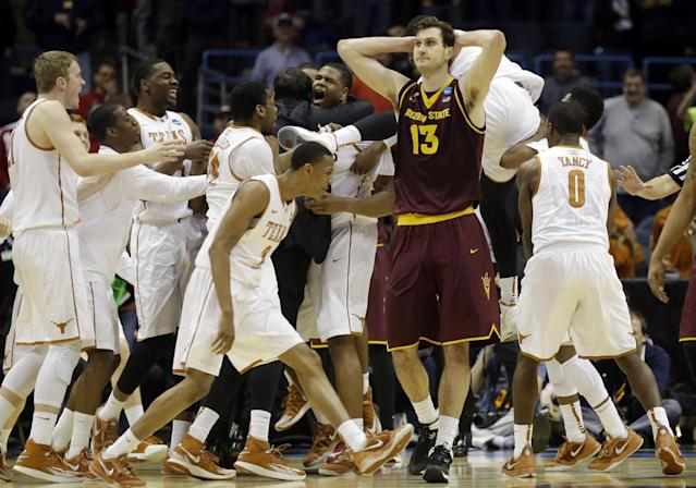 Texas players celebrates Cameron Ridley's game winning shot as Arizona State center Jordan Bachynski (13) walks off after a second-round game in the NCAA college basketball tournament Thursday, March 20, 2014, in Milwaukee. Texas won 87-85. (AP Photo/Jeffrey Phelps)