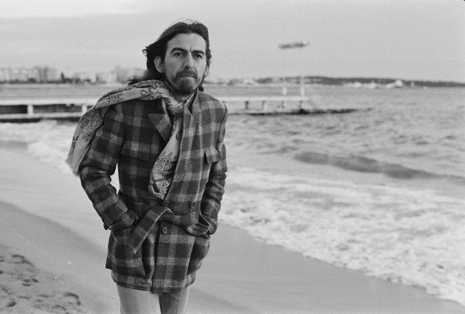 <p>George Harrison strolls along the beach in Cannes, France in 1976. </p>