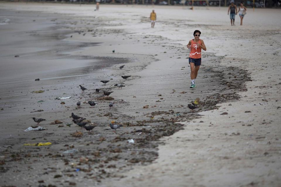 <p>A woman runs next to the trash that litters the Botafogo beach next to the Sugar Loaf mountain and the Guanabara Bay in Rio de Janeiro, Brazil, Saturday, July 30, 2016. An Associated Press investigation has found the waters where Olympians will compete in swimming and boating events next summer in South America's first games are rife with human sewage and present a serious health risk for athletes.(AP Photo/Leo Correa)</p>