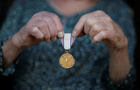 """Marthe Rigault, 87 years old, from Graignes in the Normandy region holds her medal for """"distinguished civilian service to the United States army"""" as she attends an interview with Reuters in Graignes, France May 15, 2019. Picture taken May 15, 2019. REUTERS/Christian Hartmann"""