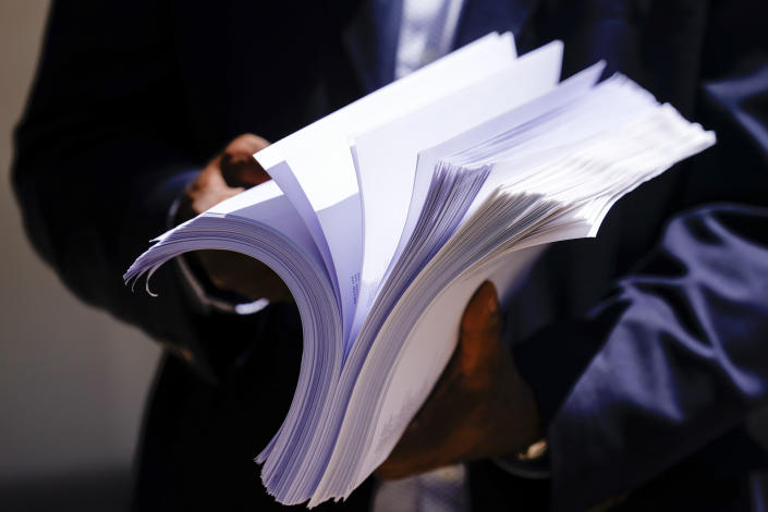 """Former NFL player Ken Jenkins holds thousands of petitions demanding equal treatment for everyone involved in the settlement of concussion claims against the NFL, before delivering them to the federal courthouse in Philadelphia, Friday, May 14, 2021. Thousands of retired Black professional football players, their families and supporters are demanding an end to the controversial use of """"race-norming"""" to determine which players are eligible for payouts in the NFL's $1 billion settlement of brain injury claims, a system experts say is discriminatory. (AP Photo/Matt Rourke)"""