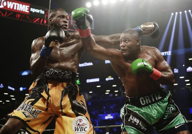 Deontay Wilder (L) and Luis Ortiz trade punches during the third round of the WBC heavyweight championship bout Saturday, March 3, 2018, in New York. Wilder stopped Ortiz in the 10th round. (AP Photo/Frank Franklin II)