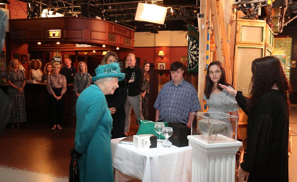 """The queen met actors and crew during a visit to the set of long-running TV series """"Coronation Street,"""" including popping into the set's Rovers Return pub, on July 8, 2021 in Manchester."""