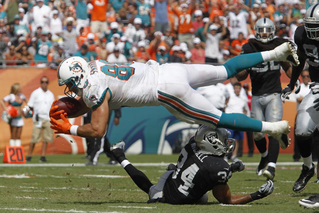 Miami Dolphins' Anthony Fasano leaps into th eendzone to score at the expense of Oakland Raiders' Mike Mitchell during their NFL football game in Miami Gardens, Florida September 16, 2012. REUTERS/Andrew Innerarity (UNITED STATES - Tags: SPORT FOOTBALL)