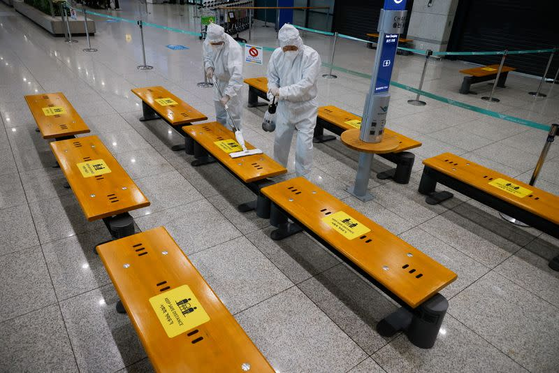 Workers wearing protective gear disinfect an arrival gate at the Incheon International Airport in Incheon