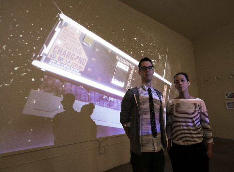 Jon Gibson and Amanda White pose with a projected image of their artwork that will be launched into space, at their studio in the Echo Park district of Los Angeles Wednesday, July 31, 2013. They believe it will be the first work of art etched into the side of a satellite that a British company is scheduled to send into orbit on Oct. 29 aboard a Soyuz rocket to be launched from Kazakhstan. (AP Photo/Reed Saxon)