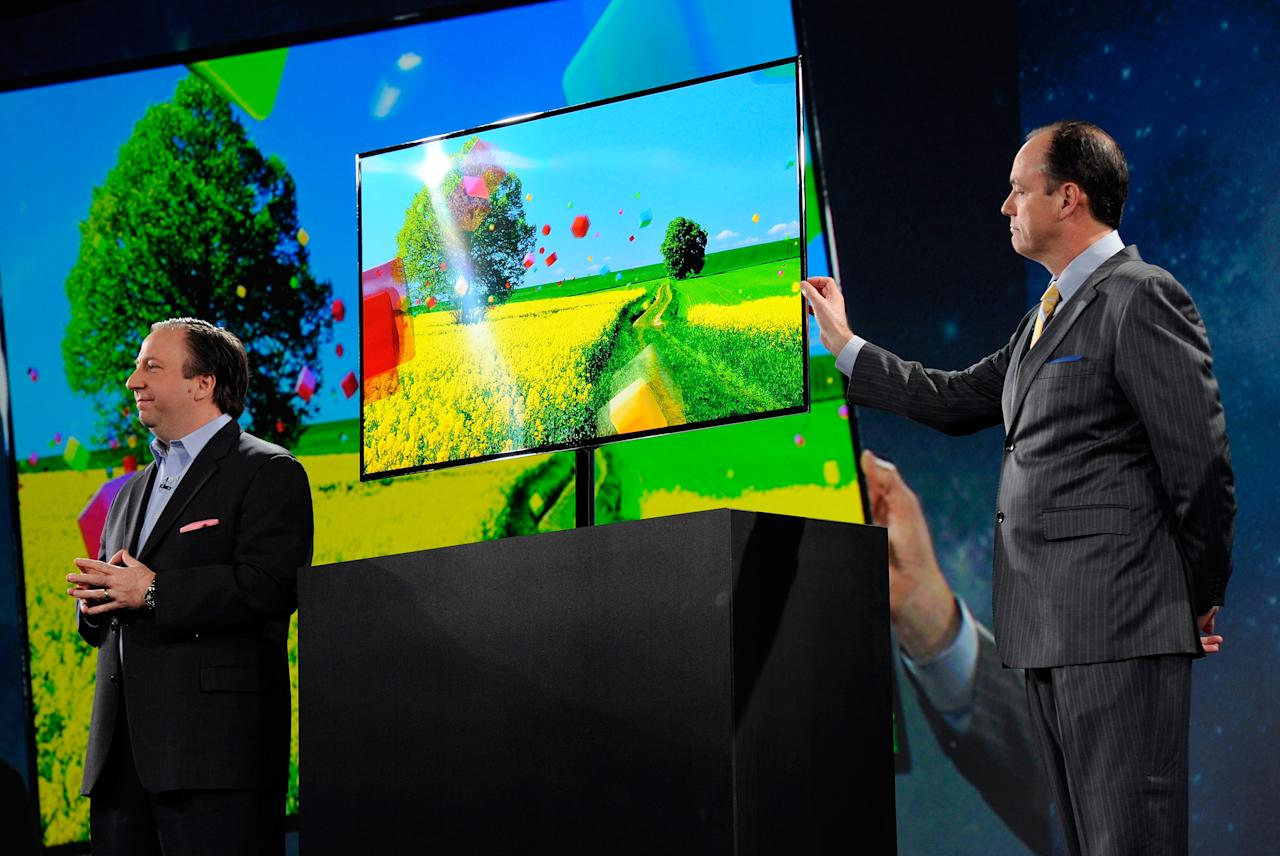 LAS VEGAS, NV - JANUARY 09:  Samsung Electronics America Senior Vice President Joe Stinziano (L) and President of Consumer Electronics for Samsung Electronics America Tim Baxter show a Samsung 55-inch super OLED TV during a press event at The Venetian for the 2012 International Consumer Electronics Show (CES) January 9, 2012 in Las Vegas, Nevada. CES, the world's largest annual consumer technology trade show, runs from January 10-13 and is expected to feature 2,700 exhibitors showing off their latest products and services to about 140,000 attendees.  (Photo by Ethan Miller/Getty Images)