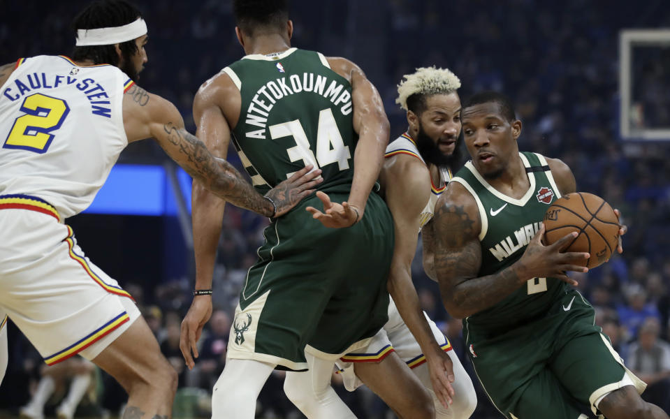 Milwaukee Bucks' Eric Bledsoe, right, drives the ball around Golden State Warriors' Ky Bowman, second from right, during the first half of an NBA basketball game Wednesday, Jan. 8, 2020, in San Francisco. (AP Photo/Ben Margot)