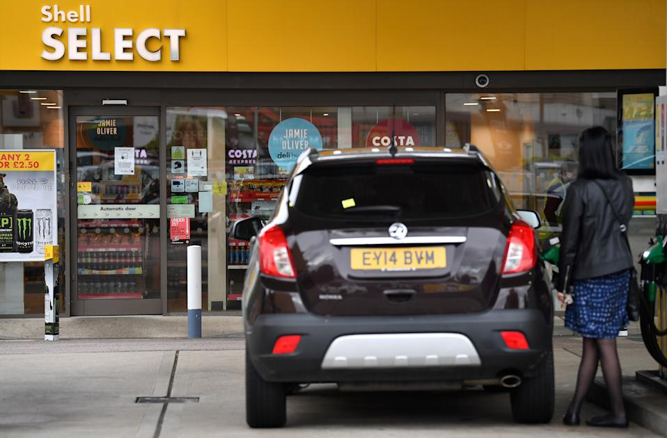 A customer refuels their car at a Shell petrol station in Etlham, southeast London on September 30, 2020. - Royal Dutch Shell will axe up to 9,000 jobs or more than 10 percent of its global workforce, the energy giant said Wednesday as the coronavirus pandemic slams oil demand and prices. The Anglo-Dutch group will cut between 7,000 and 9,000 positions by the end of 2022, including 1,500 staff who have agreed to take voluntary redundancy this year, it said in a statement. (Photo by Ben STANSALL / AFP) (Photo by BEN STANSALL/AFP via Getty Images)