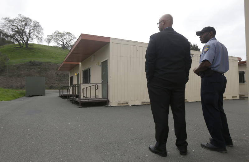 Adam Taylor, executive director of kindergarten through 12th grade school operations for West Contra Costa Unified School District, left, stands next to a security officer in front of the health clinic at the Hercules Middle-High School campus in Hercules, Calif., Tuesday, March 4, 2014. Police on Tuesday were investigating reports of a brutal assault of a transgender teen who was using a high school bathroom in a San Francisco Bay Area suburb. The 15-year-old student told officers he was leaving a boy's bathroom at Hercules High School on Monday when three teenage boys pushed him inside a handicapped stall and physically and sexually assaulted him, Hercules police Detective Connie Van Putten said. (AP Photo/Jeff Chiu)