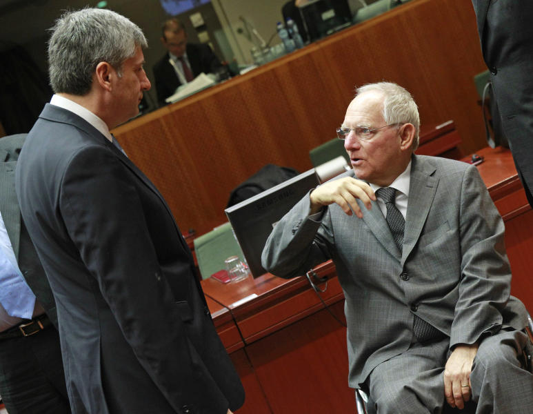 German Finance Minister Wolfgang Schaeuble, right, talks with Austrian Finance Minister Michael Spindelegger, prior to the start of the EU finance ministers meeting at the European Council building in Brussels, Tuesday, Feb. 18, 2014. (AP Photo/Yves Logghe)