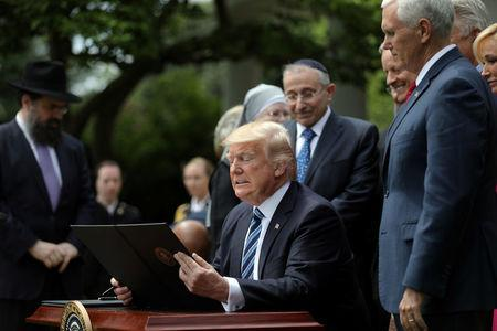 U.S. President Donald Trump prepares to sign the Executive Order on Promoting Free Speech and Religious Liberty during the National Day of Prayer event at the Rose Garden of the White House in Washington D.C., U.S., May 4, 2017. REUTERS/Carlos Barria