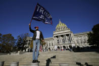 A demonstrator waves a flag supporting President Donald Trump outside the Pennsylvania State Capitol, Friday, Nov. 6, 2020, in Harrisburg, Pa., as vote counting continues following Tuesday's election. (AP Photo/Julio Cortez)