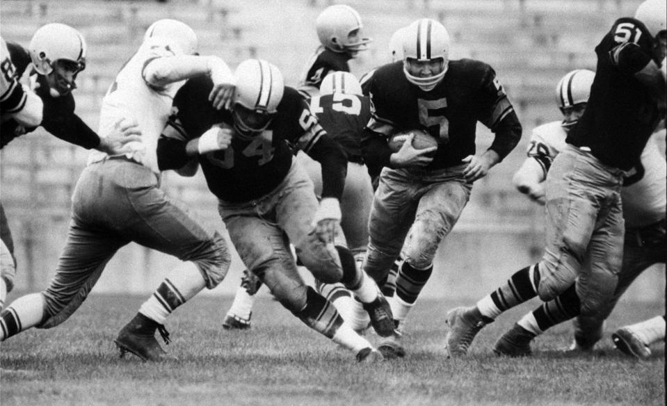 "FILE - In this Aug. 10, 1959 file photo, Paul Hornung (5) of the Green Bay Packers goes through the line in an inter-squad game in Green Bay, Wis. Hornung, the dazzling ""Golden Boy"" of the Green Bay Packers whose singular ability to generate points as a runner, receiver, quarterback, and kicker helped turn them into an NFL dynasty, has died, Friday, Nov. 13, 2020. He was 84. (AP Photo, File)"