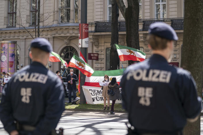 FILE - In this April 9, 2021 file photo, protesters with the Lion and Sun flag of the National Council of Resistance of Iran, an Iranian opposition group, and police officers stand near the 'Grand Hotel Wien' in Vienna, Austria, where closed-door nuclear talks with Iran take place. Negotiations to bring the United States back into a landmark nuclear deal with Iran are set to resume Thursday, April 15, in Vienna amid signs of progress — but also under the shadow of an attack this week on Iran's main nuclear facility. (AP Photo/Florian Schroetter, File)