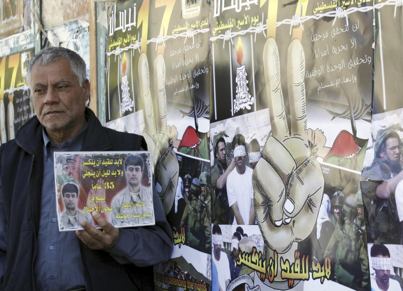A man holds a picture of a Palestinian jailed in Israel, during a rally marking the annual prisoners' day in the West Bank city of Jenin, Tuesday, April 17, 2012. The Israeli prison service said Tuesday hundreds of Palestinian prisoners have launched a hunger strike to mark the Palestinians' annual prisoners day. Text on picture quotes a poem by Ibrahim Tokan. (AP Photo/Mohammed Ballas)